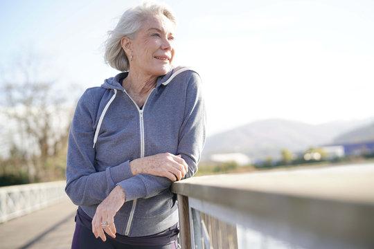 Portrait of attractive senior woman in sportswear outdoors