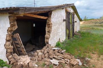 The broken wall of the abandoned brick barn
