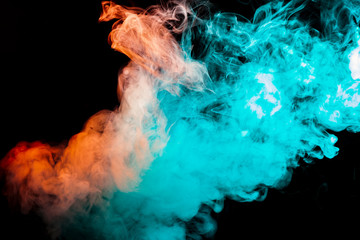 Multicolor, thick smoke, illuminated by light against a dark background, welded with clubs and curls, rising from a pair of vape.