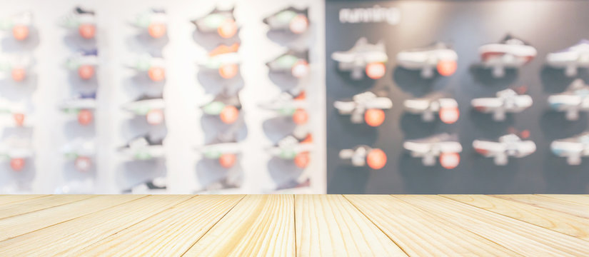 Wood table top with sneakers showcase on shelves in sport shoes store window display abstract blurred background