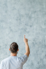 Back view of man standing on gray stucco wall background pointing up with index finger