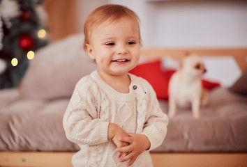 Winter holidays decorations. Warm colors. Beautiful little girl plays with present boxes before a rich decorated Christmas tree in a cozy beige room