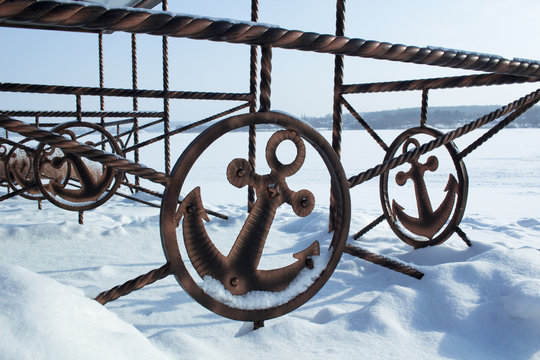 Iron sign of ancor on winter coast covered by snow