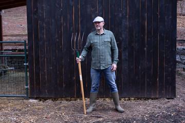 Farmer tending his goats wearing flannel against black barn.
