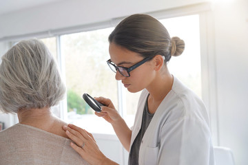 Senior woman getting skin checked by dermatologist