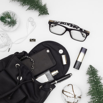 Merry Christmas and Happy newyear beauty and fashion concept. Flat lay of Christmas ornaments and black woman bag open out with accessories, smartphone on grunge white background.