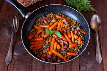 Skillet with peas, carrot, ham, spoon and fork on rustic table