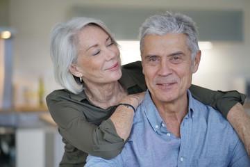 Portrait of loving senior couple in modern home