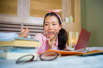 happy nerdy Asian Chinese student teenager girl in nerd hair ribbon studying at home bedroom sitting on bed with laptop computer and textbook smiling confident