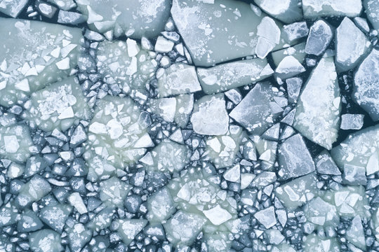 Abstract texture of broken white ice and dark water at winter. Spring is coming. Aerial view of the frozen surface.