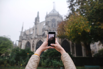 Woman taking photo of the back side of Notre dame Cathedral in Paris, France on the smartphone. Back view