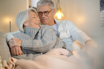 Lovely looking senior couple relaxing together on couch at home