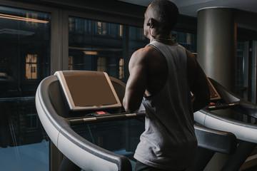 Black man running on treadmill in gym