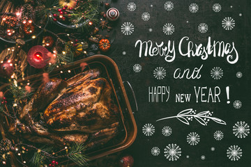 Merry Christmas and Happy New Year greeting card with text , whole roasted turkey on Christmas dinner table background with decoration and burning candles,  top view