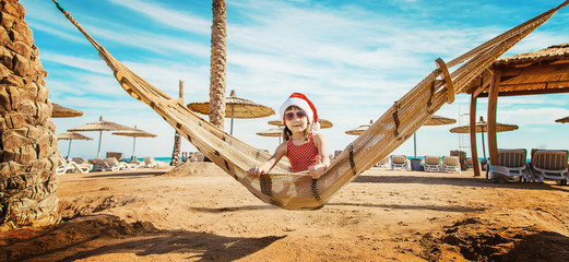 child on the beach in santa hat. Selective focus.