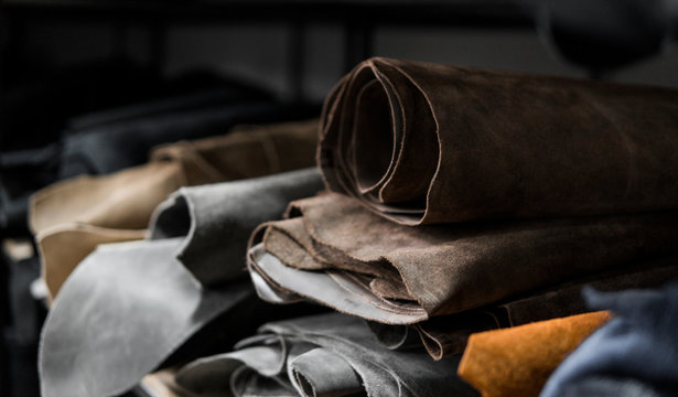 Different pieces of leather in a rolls. The pieces of the colored leathers. Rolls of natural brown and black and other leather. Raw materials for manufacture of bags, shoes, clothing and accessories.