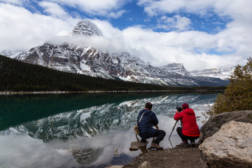 Photographers taking pictures of Beautiful Canadian Rockies Landscape during a cloudy day. Taken in Icefields Pkwy, Banff National Park, Alberta, Canada.