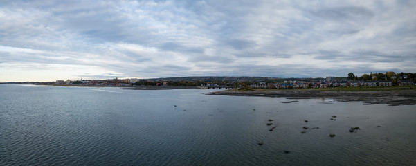 Aerial panoramic view of the small town on the the Atlantic Ocean Coast during a cloudy sunset. Taken in Rimouski, Quebec, Canada.