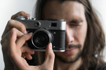 Handsome young bearded man with a long hair and in a black shirt holding vintage old-fashioned film camera on a white background and looking in camera viewfinder.