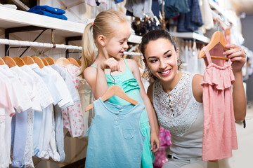 portrait of  woman and girl shopping kids apparel in clothes store