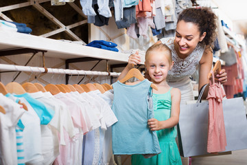 Woman with small daughter in kids apparel boutique