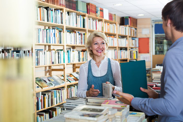 mature woman with assistant in book store.
