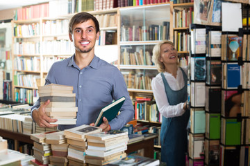 man with pile of book in book store.