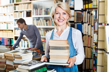 Smiling mature woman holding book pile