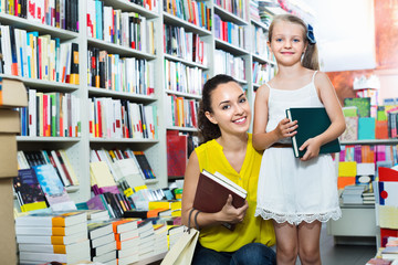 Glad woman with girl taking literature books