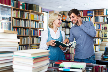 Smiling young man and mature woman holding books in hands