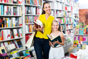 Woman showing open book to little girl