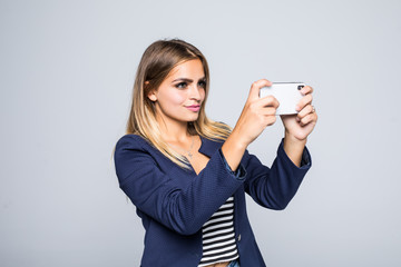 Young woman takes photographs with her mobile phone isolated on white background