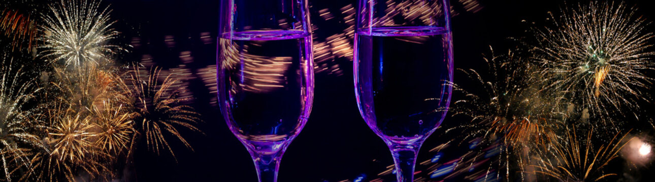 Two glasses of wine sizzling champagne with bubbles close-up on the background of colorful fireworks