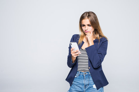 Portrait of young woman using mobile phone isolated over white background