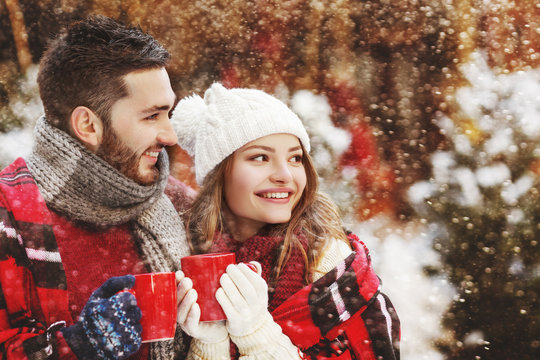 Young happy smiling couple bundle up plaid, models holding red mugs with hot drink, looking aside, posing in street. Snowfall. Christmas celebration, winter holidays concept. Copy, empty space