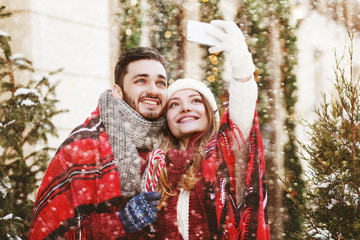Christmas selfie: young happy smiling couple takes photo on smartphone, posing on street. Models bundled up tartan blanket, holding candy canes. Snowfall. Empty, copy space for text