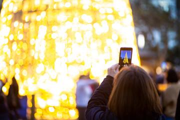 Mujer sacando foto de árbol de navidad