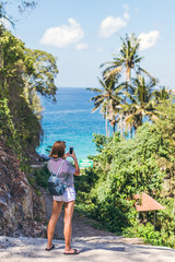 Young woman tourist taking photo of beautiful tropical landscape on her smartphone. Bali island.