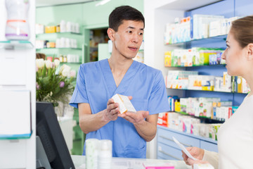 Glad woman is asking pharmacist about medicines