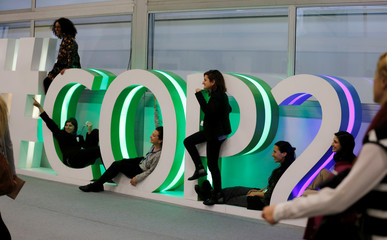 People pose for a picture inside the venue of the COP24 U.N. Climate Change Conference 2018 in Katowice