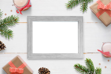 Horizontal photo frame surrounded with Christmas New Year gifts, tree branches and decorations. Isolated frame for photo mockup.