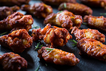 Hot and spicy chicken wings on dark background
