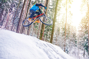 Silhouette of a cyclist in a jump. Mountain biking on trails in a snowy forest. Extreme winter sport. Bike rider flies through the air