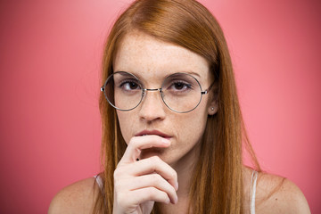 Interesting young woman with eyeglasses thinking and looking at camera over pink backgound.