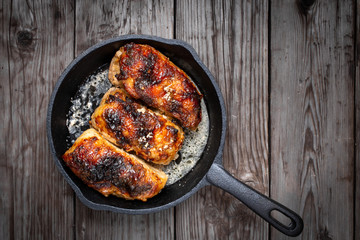 Roasted chicken pieces in cast iron pan top view