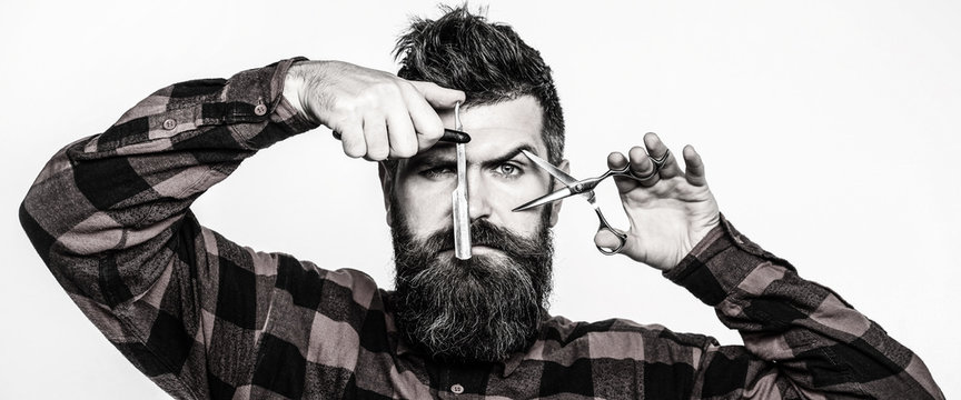 Barber scissors and straight razor, barbershop. Mens haircut, shaving. Bearded man, long beard, brutal, caucasian hipster with moustache. Vintage barbershop.