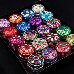 Set of Small colorful jewellery boxes decorated with glitter, sequins and zircons on dark background