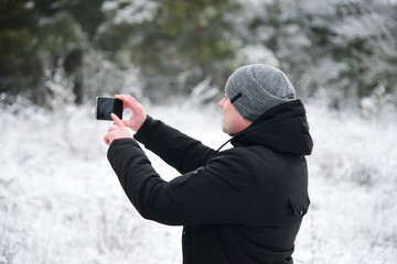 Man take photo on smart phone in winter forest