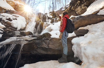 Girl looking at winter waterfall and orange sun