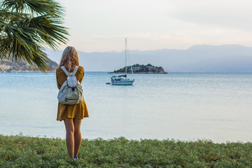 travel adult backpack girl stain back to camera under park and taking photo of beautiful tropic sea bay landscape with yacht on calm water surface and island in soft evening colors before sunset